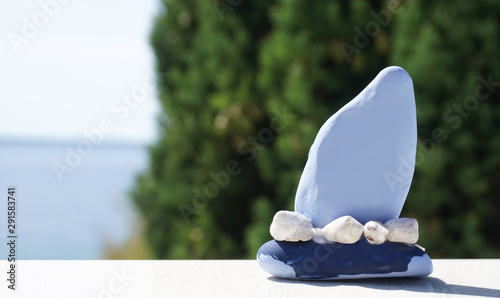 Valokuva  Blue craft boat made from small stone and seashells with nature background of gr