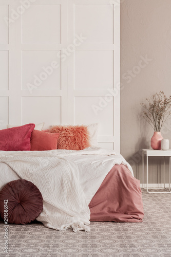 Amaranth pillow and dirty orange bedding on king size bed in fashionable bedroom Canvas Print