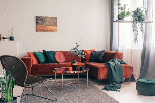 Obraz Cozy living room interior with corner sofa with pillows and painting on the wall - fototapety do salonu
