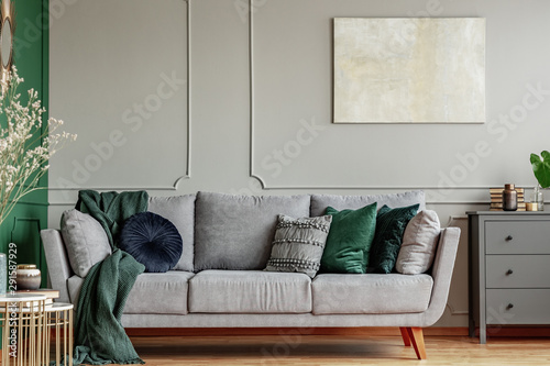 Fototapeta Pillows on long comfortable living room couch in grey scandinavian style interior with wooden floor obraz