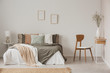 canvas print picture - Stylish chair next to warm king size bed in scandinavian bedroom