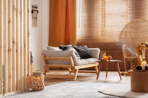 Orange candle on wooden coffee table in cozy living room interior