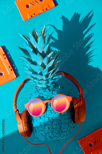 Funny pineapple in sunglasses and earphones with a shadow, flat lay on blue paper - 291589760
