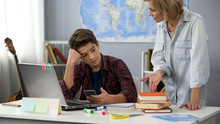 Woman Pointing At Books Scolding Son Holding Smartphone, Teen Age Behavior