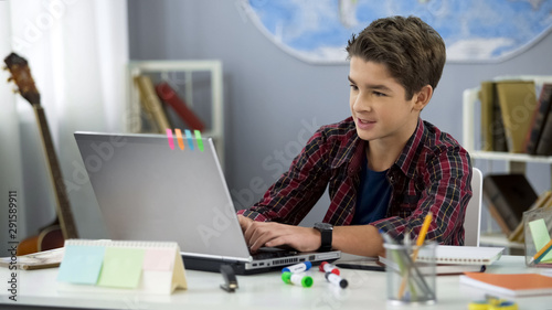 Fotomural  Schoolboy playing online game on laptop at home sitting table, teenage free time