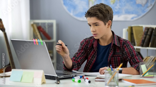 Photo Male child doing homework in room using e-book on laptop, contemporary education