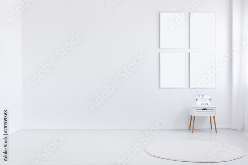 Obraz Copy space on white wall and mockup of posters in empty kid's room interior with cabinet. Real photo - fototapety do salonu