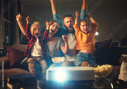 Canvas Prints Coffee bar family mother father and children watching projector, TV, movies with popcorn in evening at home