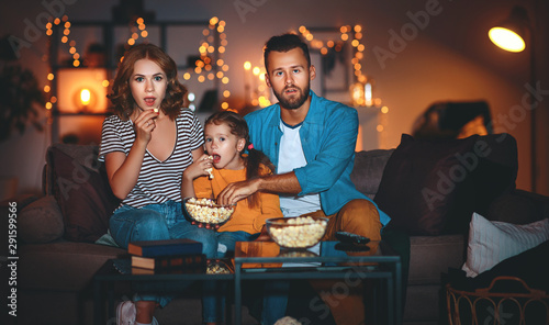 Fotografía  family mother father and child daughter watching projector, TV, movies with popcorn in   evening   at home