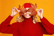 canvas print picture happy emotional cheerful girl laughing  with knitted autumn red cap  on colored yellow background.