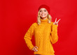 canvas print picture happy emotional cheerful girl laughing  with knitted autumn cap  on colored red background.