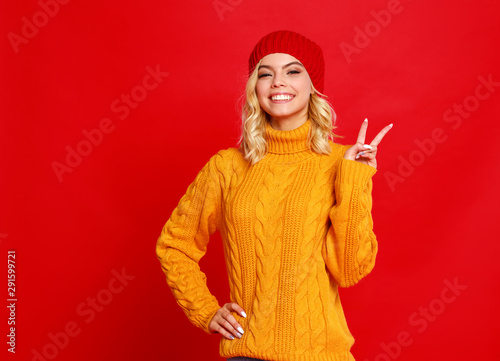 happy emotional cheerful girl laughing  with knitted autumn cap  on colored red background. - 291599721