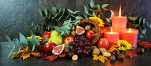 Happy Thanksgiving Cornucopia Table Setting Centerpiece Decorated With Autumn Leaves, Fruit, Nuts And Orange Burning Candles, Web Banner.