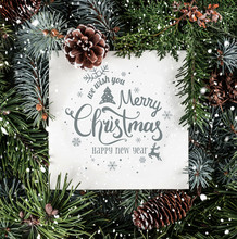 Merry Christmas And New Year Text On Paper Card Note Over Holiday Background With Fir Branches, Snow And Pine Cones. Xmas And New Year Theme. Flat Lay, Top View