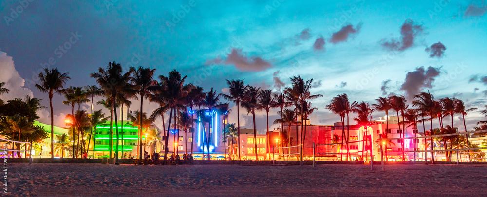 Panorama Miami Drive Ocean Drive z hotelami i restauracjami o zachodzie słońca. Panoramę miasta z palmami w nocy. Życie nocne w stylu art deco na południowej plaży