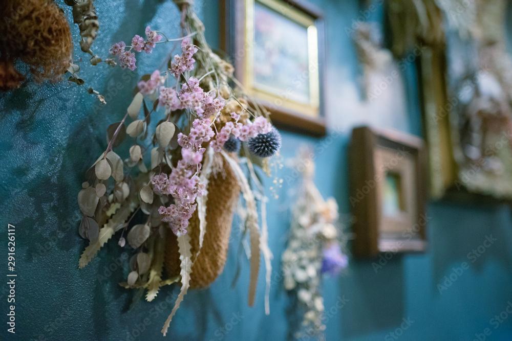 Fototapeta 青い壁にかけられたドライフラワーのスワッグと額縁