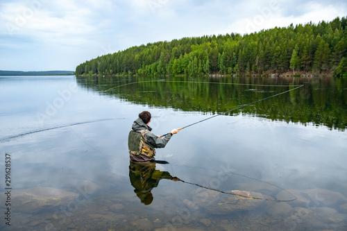 Fototapeta Fisherman using rod fly fishing in river morning sunrise splashing water
