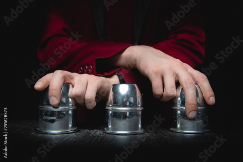 Fotomural Magician shows shell game of thimbles with circles and ball, black background