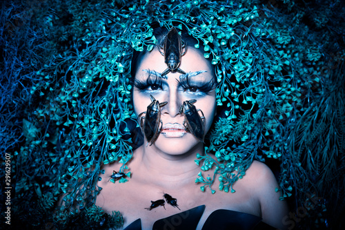 Fototapeta  Woman fantasy make up with pimps on face and cover green grass and leafs around