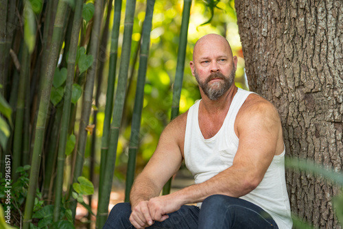 Photo sur Toile Ecole de Danse Handsome man in a tshirt sitting by a tree in the park