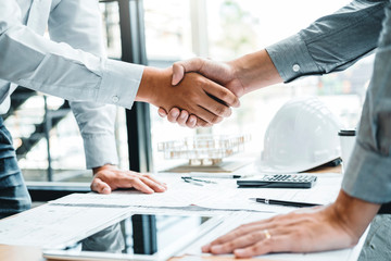 Engineer handshake meeting for architectural project and working with partner engineering on workplace