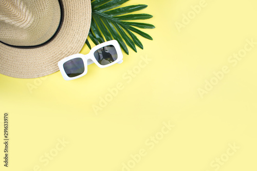 Fototapeta Top view Retro tourist equipment straw hat and sunglasses on a yellow background. Summer item. obraz na płótnie