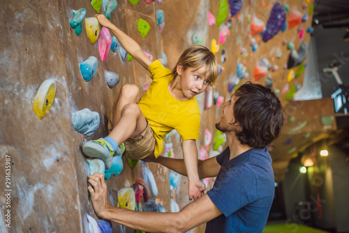 Obraz na plátně Dad and son at the climbing wall