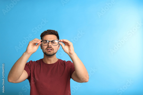 Pinturas sobre lienzo  Young man with vision problems wearing glasses on blue background, space for tex