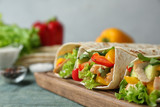 Board with delicious meat tortilla wraps on blue wooden table against grey background, closeup