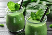 Jars Of Healthy Green Smoothie With Fresh Spinach On Grey Wooden Table, Closeup