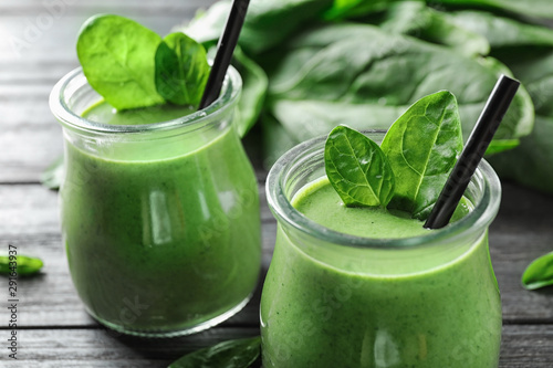 Jars of healthy green smoothie with fresh spinach on grey wooden table, closeup Canvas Print