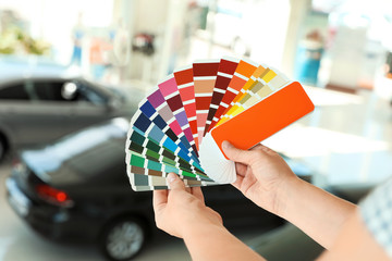 Young woman holding palette with color samples at car service station, closeup