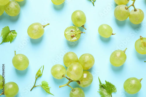 Fotografía  Flat lay composition with fresh ripe juicy grapes on light blue background