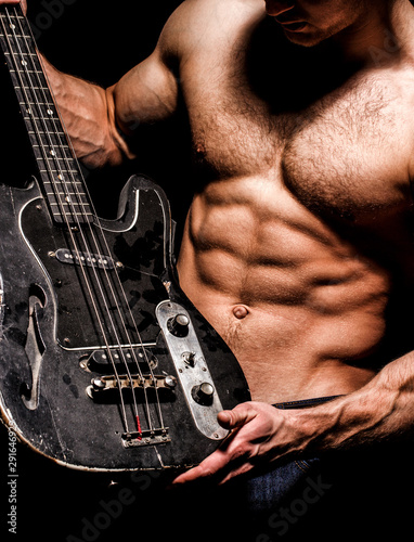 Fototapety, obrazy: Instrument on stage and band. Strong, muscular, muscles man, bodybuilding. Music concept. Electric guitar. Guitar. Torso man. Play the guitar. Chest muscle