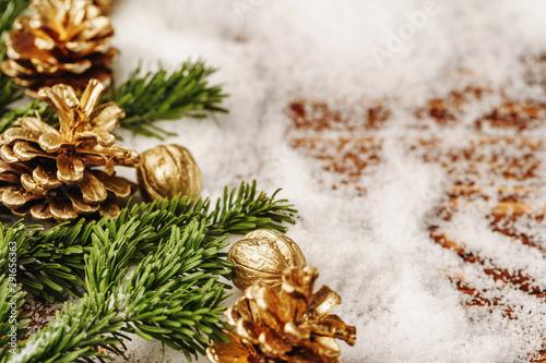 Obraz na plátně  Golden painted pine cone on snowy table, christmas decor