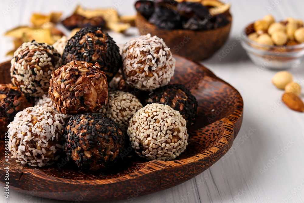 Fototapety, obrazy: Healthy energy balls of nuts, oatmeals and dried fruit with coconut, flax and sesame seeds on coconut wooden plate on a white background, horizontal orientation