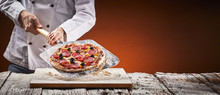Chef In A Pizzeria With Homemade Salami Pizza