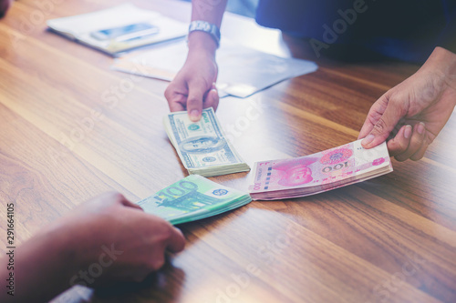 Fototapeta Business peoples holding USD dollars, yuan RMB, Euro money sharing for exchange investment obraz