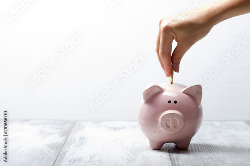 Fotografía  woman hand putting money coin into piggy for saving money wealth and financial c