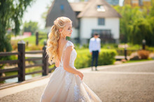 The Bride Is Waiting For The Groom Before The Meeting. Loving Wedding Couple In The Summer On The Square In The City Of Dnipro, Ukraine. The Concept Of Romantic Relationship, Idyll. Close-up Kiss And