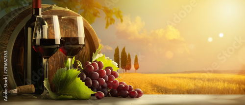 autumn countryside wine background; vine, red wine bottles, wineglass, wine barrel; wine tasting concept