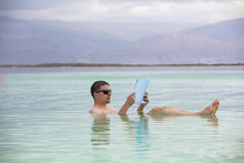 Man Swimming In The Sea And Reading A Magazine During Spa Procedures. Summertime, Holiday, Travel Concept. Dead Sea Scene