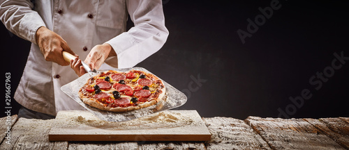 Photo Chef making a homemade pepperoni pizza