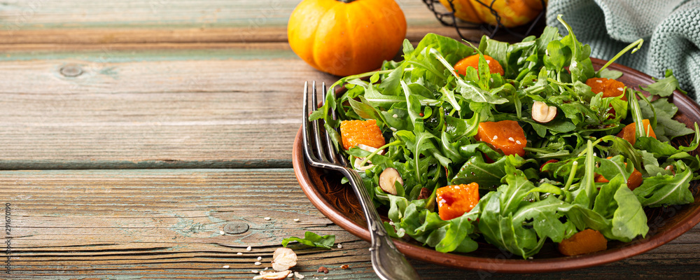 Fototapety, obrazy: Paleo diet salad with arugula, baked pumpkin, hazelnut and sesame seeds on brown plate. Healthy food concept with copy space. Banner.