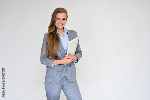 Portrait of a beautiful manager girl in a gray business suit on a white background with a folder in her hands Tablou Canvas