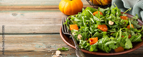 Cuadros en Lienzo  Paleo diet salad with arugula, baked pumpkin, hazelnut and sesame seeds on brown plate