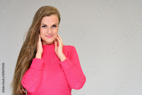 Close-up portrait of a beautiful girl with long hair in a coral sweater on a white background Fototapet