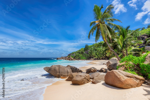 Exotic Sunny beach and coconut palms on Seychelles. Summer vacation and tropical beach concept.