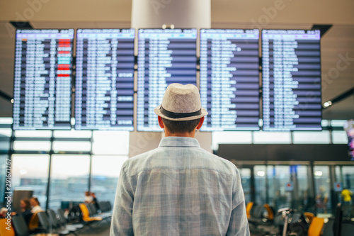 Photo Solo traveler - man standing inside airport terminal looking at a schedule