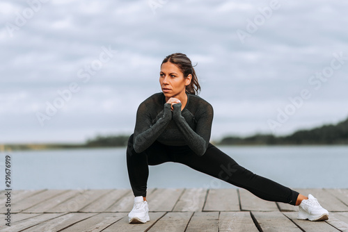 Front view of a fit woman doing side lunges near the river. Wallpaper Mural